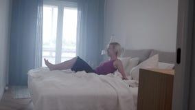 Movimento lento della donna felice che salta e che cade sul letto in suo appartamento, carrello dentro archivi video