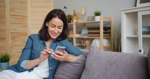 Movimento lento della donna graziosa che sorride ottenendo buone notizie che esaminano smartphone stock footage