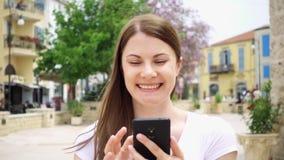 Movimento lento Della donna della passeggiata via giù in città europea facendo uso del cellulare, passando in rassegna, chiacchie video d archivio