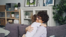 Movimento lento della madre di amore e di piccolo figlio che abbracciano seduta sul sofà a casa video d archivio