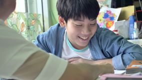 Movimento lento della madre felice e del figlio asiatici che fanno il vostro compito con il fronte di sorriso 4K stock footage