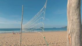 Movimento lento della pentola sparato sopra la rete di pallavolo sulla spiaggia tropicale il giorno soleggiato Cielo blu di Ameri video d archivio