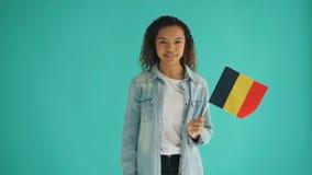 Movimento lento della ragazza afroamericana sveglia che tiene bandiera tedesca e sorridere archivi video