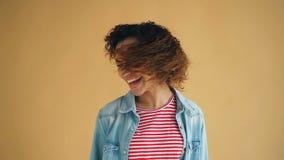 Movimento lento della ragazza attraente della corsa mista che scuote testa che ondeggia capelli ricci stock footage