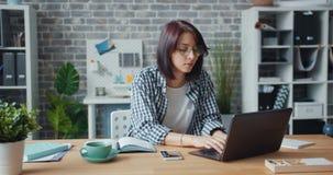 Movimento lento della ragazza graziosa che lavora nell'ufficio facendo uso della seduta di battitura a macchina del computer port archivi video