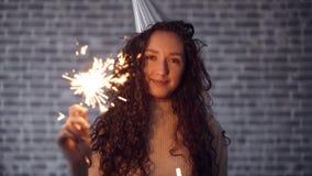 Movimento lento della ragazza nella stella filante della tenuta del cappello del partito che sorride sul fondo del mattone video d archivio