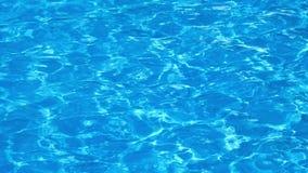 Movimento lento della superficie blu e luminosa dell'acqua dell'ondulazione nella piscina con la riflessione del sole, HD pieno video d archivio