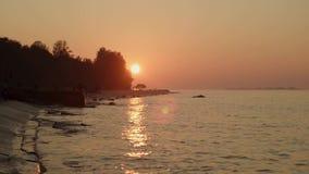 Movimento lento delle onde calme del fiume al tramonto sotto il cielo arancio ad estate stock footage