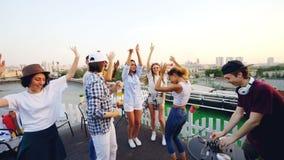 Movimento lento delle ragazze trascurate e dei tipi che ballano sul tetto e sulla soda bevente mentre il DJ sta regolando Digital stock footage