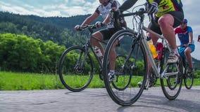 Movimento lento di angolo basso dei concorrenti della corsa del ciclo