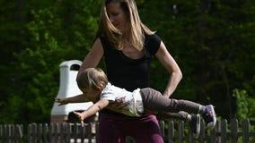 Movimento lento di giovane madre felice che gioca con sua figlia del bambino archivi video