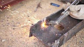 Movimento lento di taglio del ferro con la torcia del gas sul lavoro nel cantiere stock footage