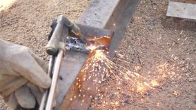 Movimento lento di taglio del ferro con la torcia del gas sul lavoro nel cantiere video d archivio