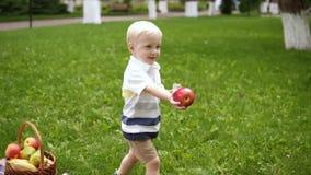 Movimento lento di un funzionamento blondy del ragazzo su un'erba verde Prende una mela rossa dal canestro e dalle elasticità di  stock footage