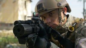 Movimento lento di un soldato con la pistola e la cuffia avricolare che sta tendendo l'obiettivo nell'operazione tattica pronta p archivi video