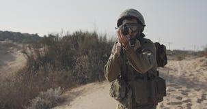 Movimento lento di un soldato israeliano che cammina con un fucile su una collina della sabbia archivi video