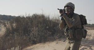 Movimento lento di un soldato israeliano che cammina con un fucile su una collina della sabbia video d archivio