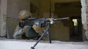 Movimento lento di un soldato munito in cammuffamento con il fucile della mitragliatrice che guarda dalla finestra stock footage