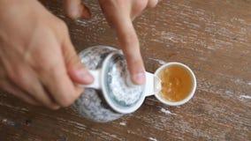 Movimento lento di versamento del tè verde sano dalla teiera d'annata in tazza sulla Tabella di legno Cerimonia del cinese tradiz archivi video