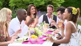 Movimento lento disparado dos amigos que apreciam o partido de jantar exterior video estoque