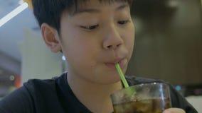 Movimento lento do adolescente que bebe um vidro de refrescar a bebida efervescente fria da cola com cara do sorriso vídeos de arquivo
