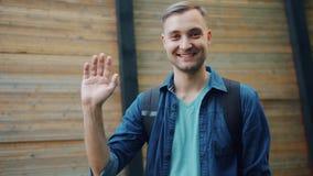 Movimento lento do ar livre de ondulação de sorriso da mão do homem atrativo no fundo de madeira filme
