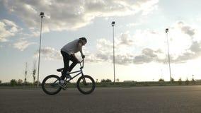 Movimento lento do ciclista atlético talentoso que exercita um salto da rotação do meio do ar no ciclo na parte externa da trilha video estoque