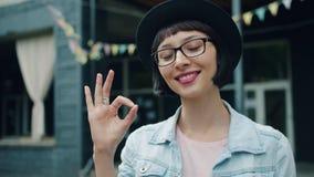 Movimento lento do gesto da APROVAÇÃO da exibição da jovem senhora fora da câmera de vista de sorriso vídeos de arquivo
