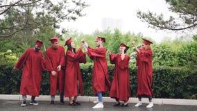 Movimento lento do grupo multi-étnico de estudantes nos vestidos e de almofariz-placas que dançam e que riem fora no terreno sobr vídeos de arquivo