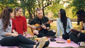 Movimento lento do guitarrista do homem novo que canta e que joga a guitarra fora no piquenique quando seus amigos escutarem vídeos de arquivo