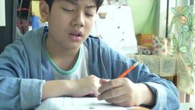 Movimento lento do menino asiático bonito que faz seus trabalhos de casa com cara irritada 4K video estoque