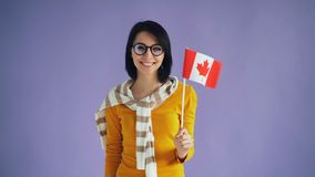 Movimento lento do moderno canadense que guarda a bandeira nacional que sorri olhando a câmera video estoque