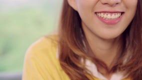 Movimento lento - do sentimento asiático da mulher do adolescente sorriso feliz e vista ao quando da câmera para relaxar em casa  vídeos de arquivo