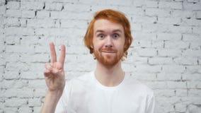 Movimento lento do sinal da vitória pelo homem da barba no escritório filme