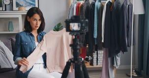 Movimento lento do vídeo da gravação do blogger da forma sobre a roupa em casa que fala vídeos de arquivo