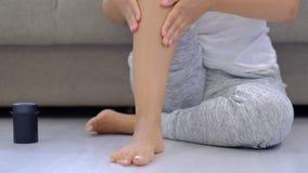 Movimento lento Donna che sfrega i piedi gonfiati stanchi, vene varicose Massaggio facente femminile del piede a casa dopo una gi archivi video