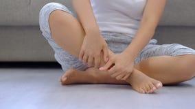 Movimento lento Donna che sfrega i piedi gonfiati stanchi, vene varicose Massaggio facente femminile del piede a casa dopo una gi video d archivio