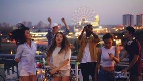 Movimento lento dos jovens atrativos que dançam no telhado que aprecia o partido quando o indivíduo considerável do DJ misturar a vídeos de arquivo