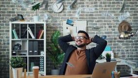 Movimento lento dos lotes do dinheiro que caem no indivíduo de meia idade considerável no escritório video estoque