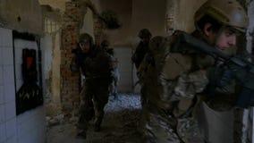 Movimento lento dos soldados militares que correm em uma construção arruinada para praticar a formação das manobras vídeos de arquivo