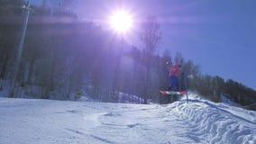 MOVIMENTO LENTO: Giovane pro snowboarder che guida il mezzo tubo nel grande parco della neve della montagna, neve di spruzzatura  archivi video