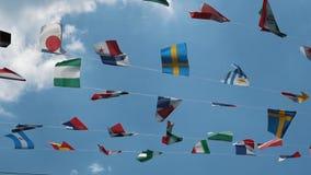 Movimento lento, gruppo di bandiere dei cittadini a cielo blu con le nuvole bianche Bandiere di molti paesi del mondo nell'aria stock footage