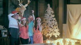 Movimento lento Gruppo felice di amici alle mani d'ondeggiamento di una festa di Natale, sorridente nella macchina fotografica stock footage