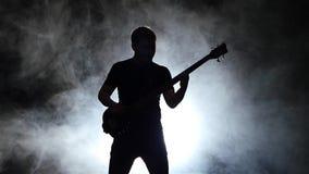 Movimento lento Homem baixo do guitarrista da silhueta no fumo Fundo preto vídeos de arquivo