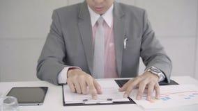 Movimento lento - homem de negócios virado na mesa no escritório Homem de negócios asiático que está sendo comprimido trabalhando vídeos de arquivo