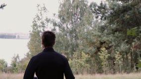 Movimento lento Homem que corre através das madeiras profundas A câmera segue a saída masculina nova da floresta à costa cênico d filme