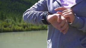 Movimento lento Il funzionamento e lo sguardo della giovane donna di sport di salute indossano il dispositivo astuto dell'orologi video d archivio
