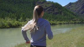 Movimento lento Il funzionamento e lo sguardo della giovane donna di sport di salute indossano il dispositivo astuto dell'orologi archivi video