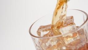 MOVIMENTO LENTO: Il whiskey versa dentro un vetro con cubetti di ghiaccio su fondo bianco - alto vicino video d archivio