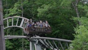 MOVIMENTO LENTO: La gente che guida le montagne russe 4k stock footage
